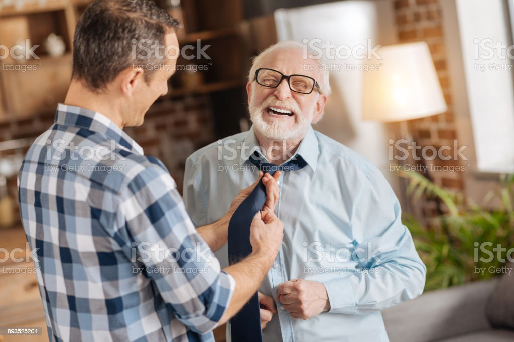 Young man tying the tie of his elderly father stock photo