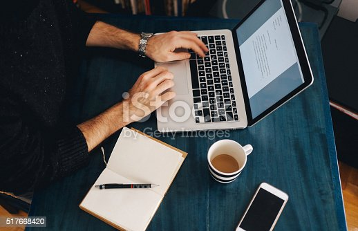 istock Young man typing at the laptop 517668420