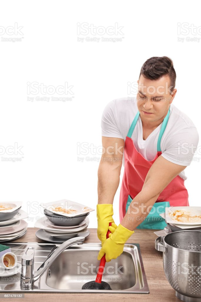 Young man unclogging a sink with a plunger stock photo