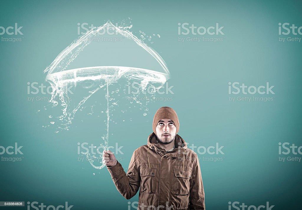 Young man under an umbrella stock photo