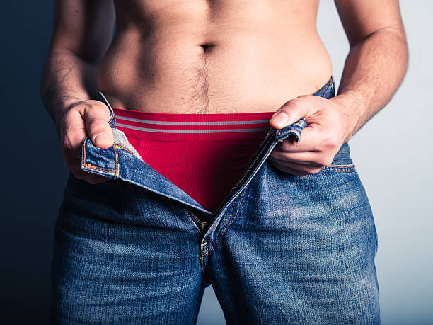Young man undoing his pants A young man is undoing his pants underwear male stock pictures, royalty-free photos & images