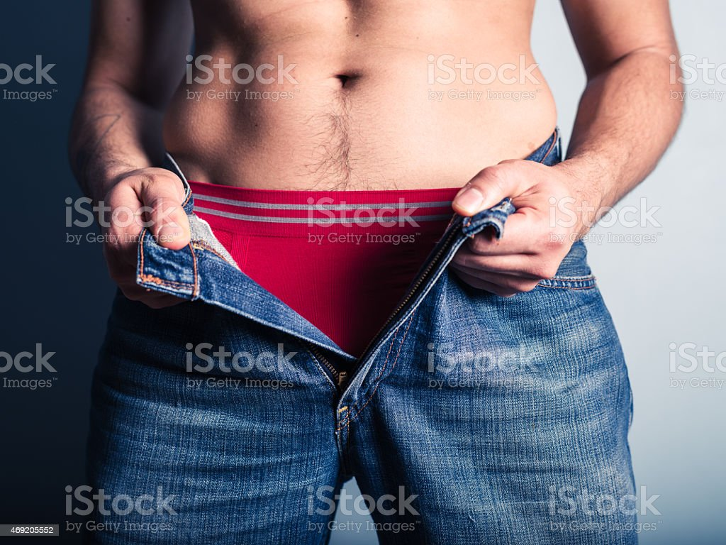 Young man undoing his pants stock photo