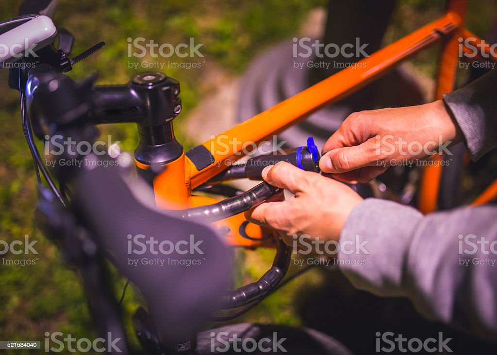 Young man unlocks his bicycle outdoors stock photo