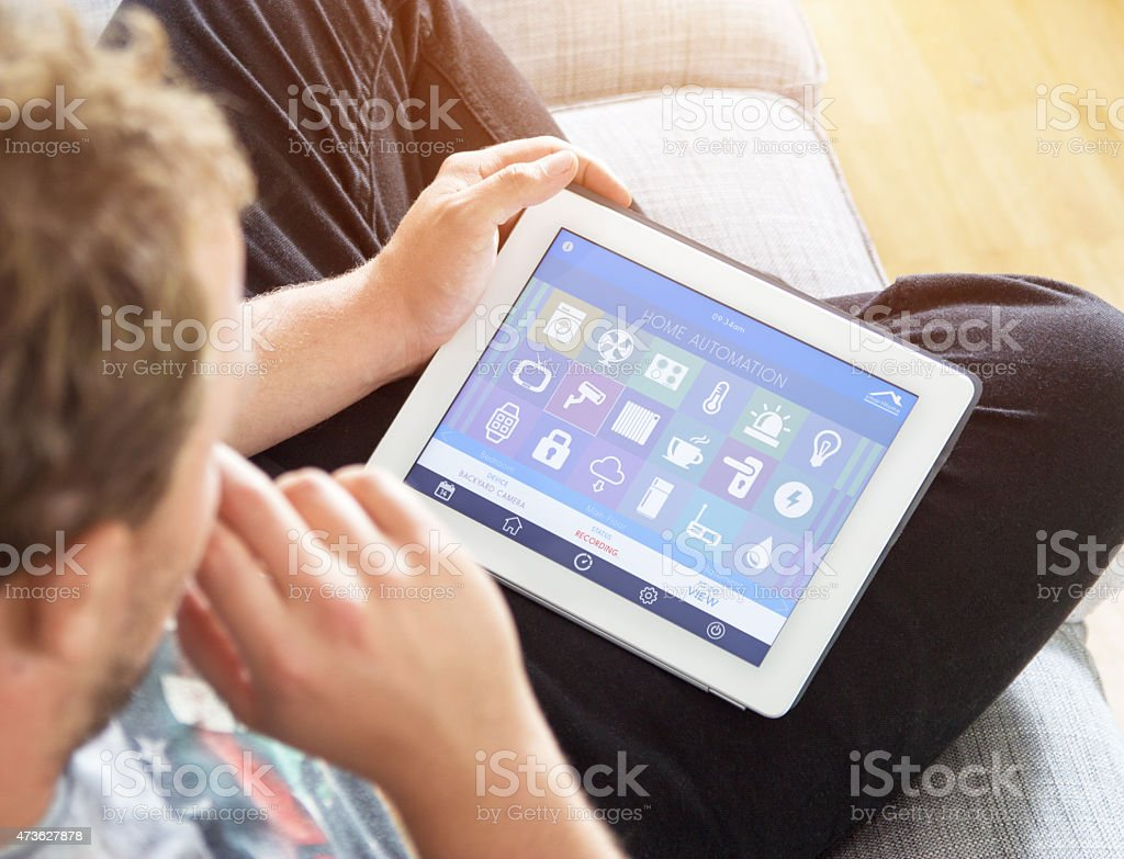 Young man use a tablet for smart home control stock photo