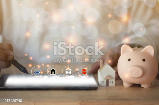 Young man use digital pen for drawing visual planning for family future with tablet, miniature home and pink piggy bank. Concept of planning family future