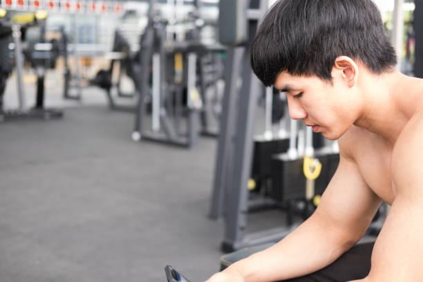 jongeman mobiele telefoon gebruiken in het fitnesscentrum. mannelijke atleet tekstbericht in mobiel in de sportschool. sportieve kerel check sociale nieuws in slimme telefoon in healthclub na uit te werken. - call center stockfoto's en -beelden
