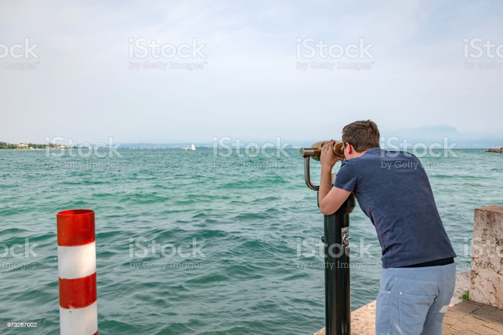 Young man uses a telescope looking over Lake Garda, Italy stock photo
