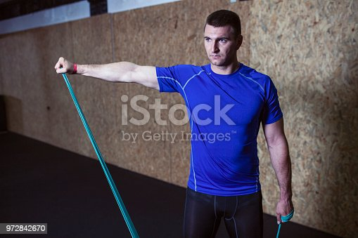 1069872470 istock photo Young man uses rope to stretch 972842670