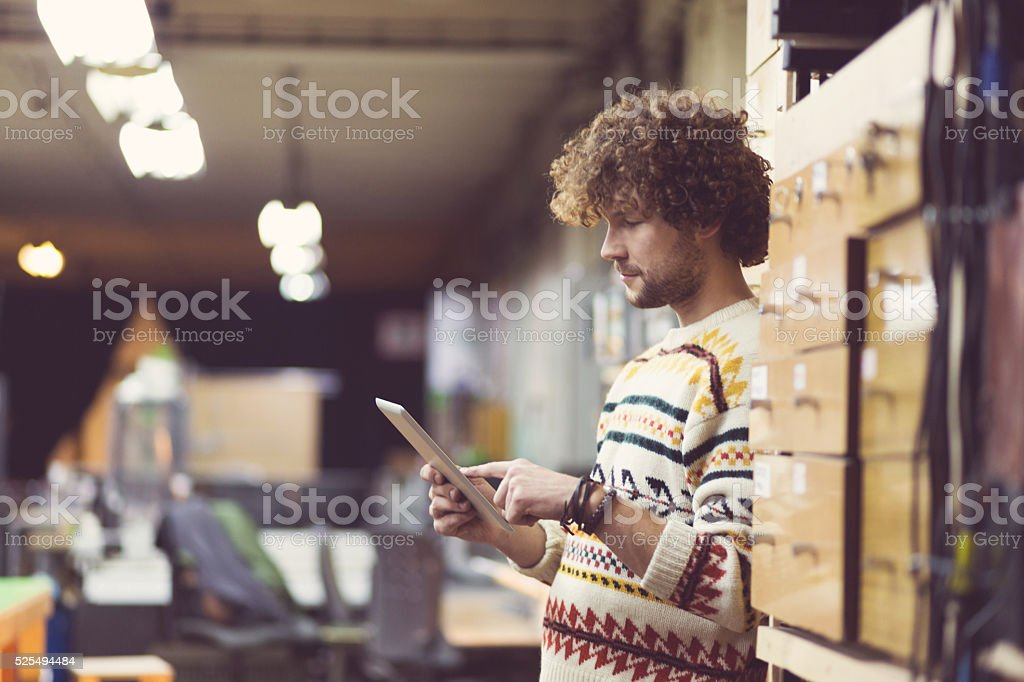 Young man using a digital tablet in a workshop stock photo