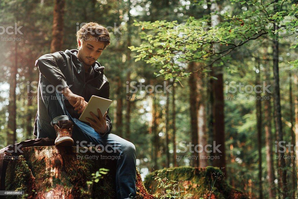 Jovem usando um tablet digital na floresta - foto de acervo