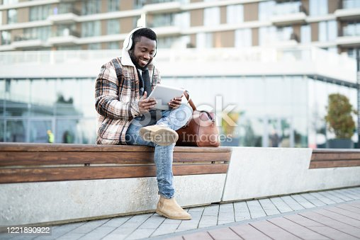 African American man watching content on a digital tablet outdoors.