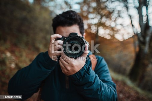 Young man using a DSLR camera in a forest in autumn