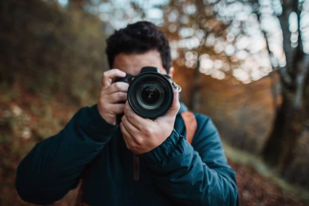jonge man met behulp van een dslr-camera in een bos in de herfst - spiegelreflexcamera stockfoto's en -beelden