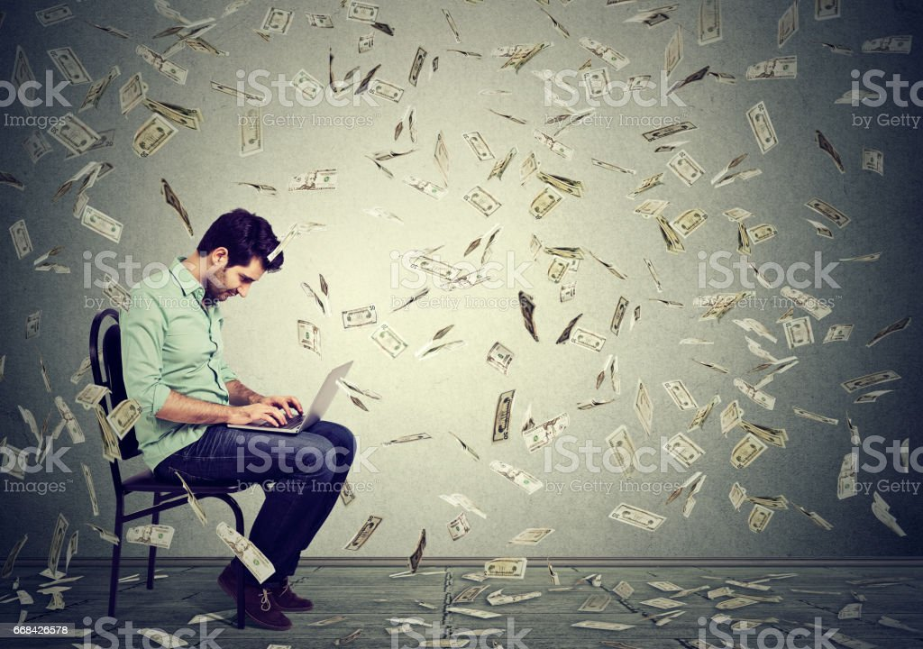 Young man using a laptop building online business making dollar bills cash falling down - foto stock