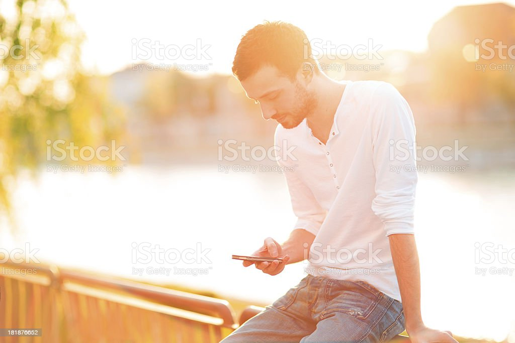 Young man using a smart phone outdoors royalty-free stock photo