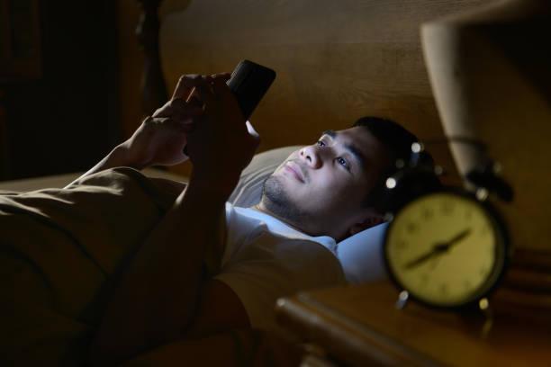 junger mann mit einem smartphone in seinem bett in der nacht - mann sucht mann stock-fotos und bilder