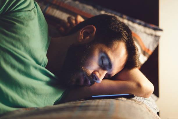 young man using a smartphone in his bed - männliches schlafzimmer stock-fotos und bilder
