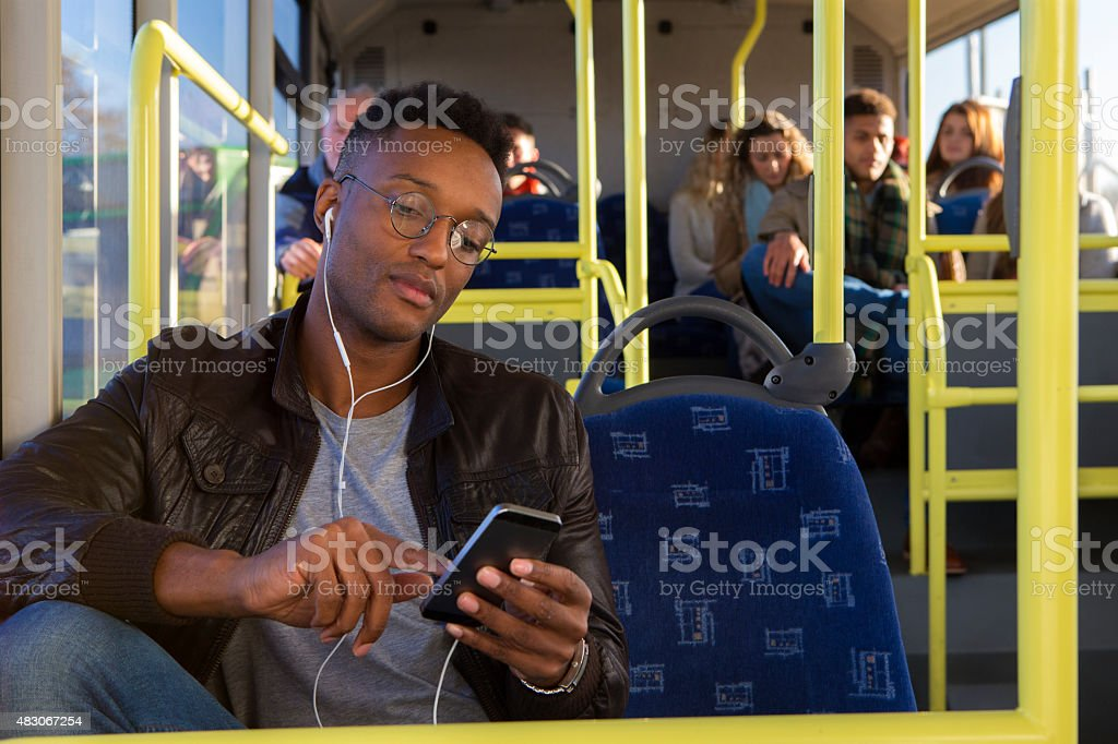 Young man using a smartphone on the bus stock photo