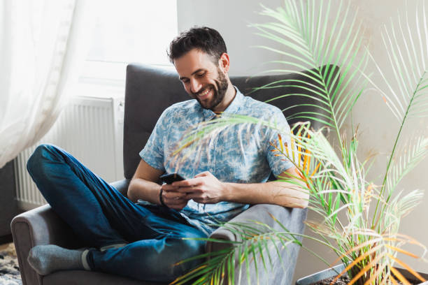 Young man using a smartphone stock photo