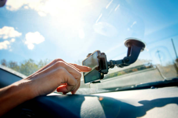 young man using a smpartphone while driving a car - rideshare stock photos and pictures