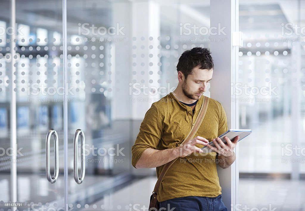 Young man using a tablet at airport royalty-free stock photo