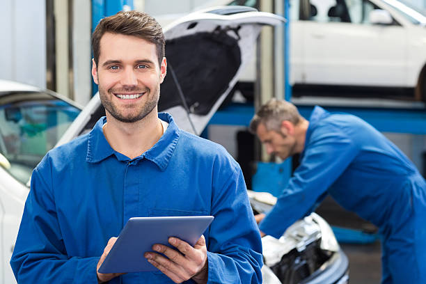 Young man using a tablet in a mechanic's workshop Smiling mechanic using a tablet pc at the repair garage mechanic stock pictures, royalty-free photos & images