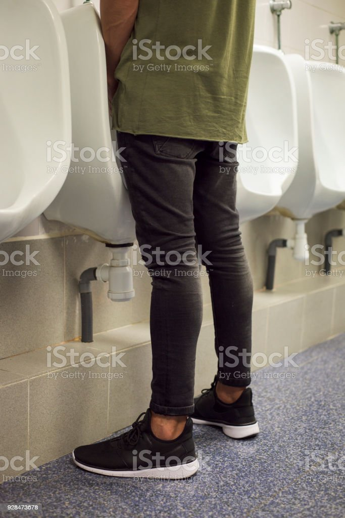 young man using a urinal in a public washroom stock photo