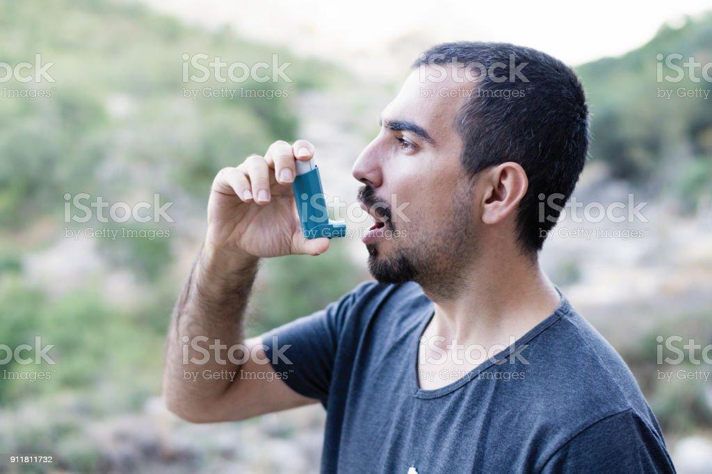 Young man using an asthma inhaler stock photo