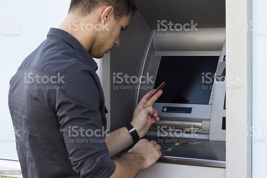 Young man using ATM stock photo