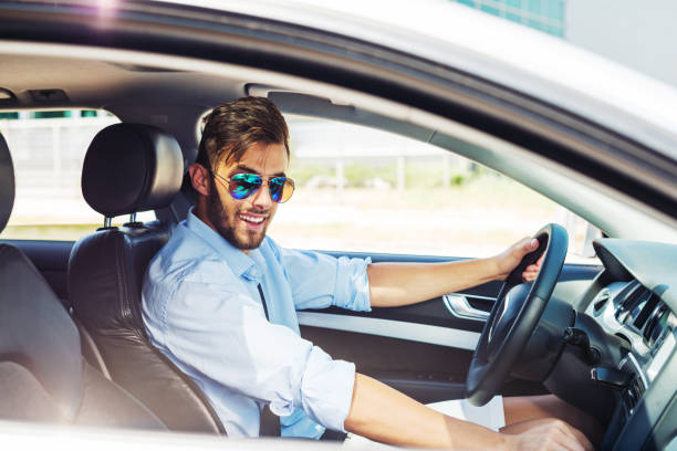 Young man using car pooling service stock photo
