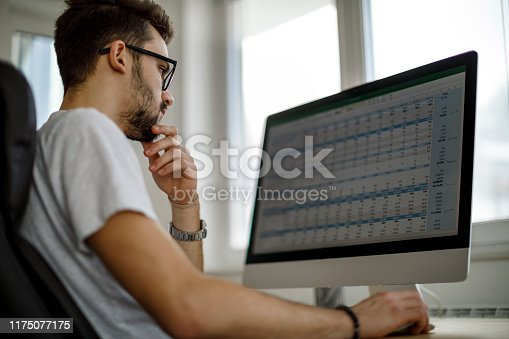 1098316816 istock photo Young man using computer at home 1175077175