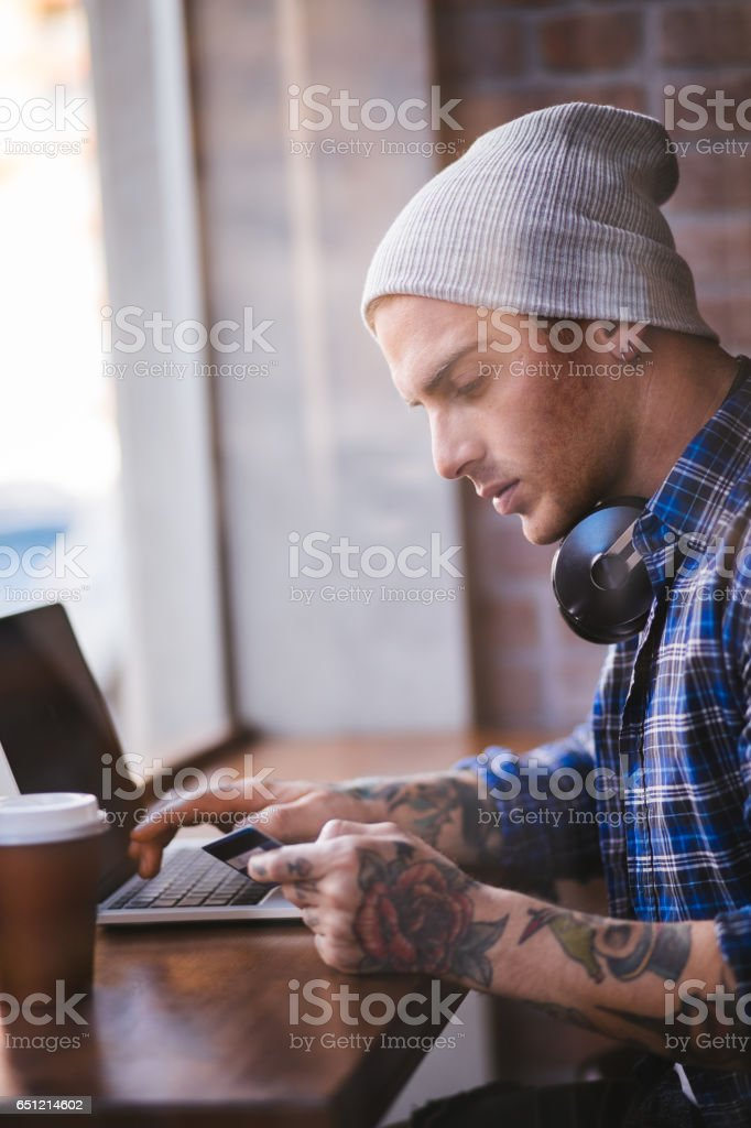 Young man using credit card to shop online stock photo