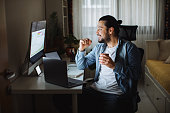istock Young man using desktop pc at desk in home office 1310344261