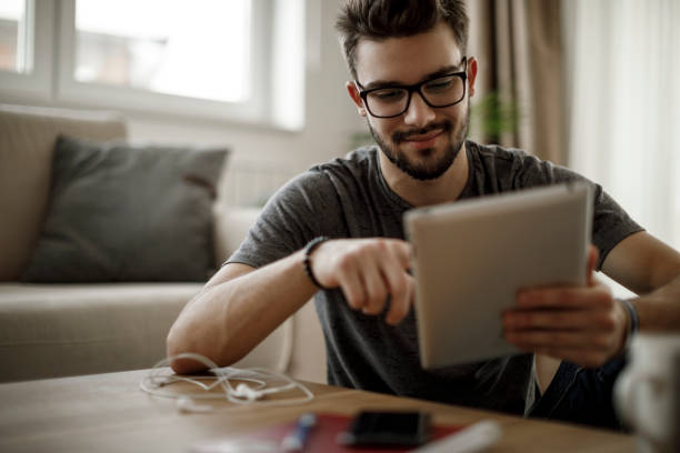Young man using digital tablet at home stock photo