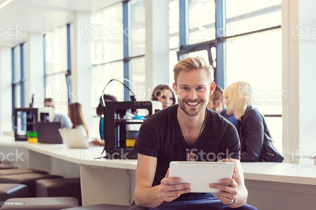 Young man using digital tablet in 3D printer office Start-up Business. Focus on confident young man using a digital tablet and smiling at camera with group of people using 3D printer in the background. 2015 Stock Photo