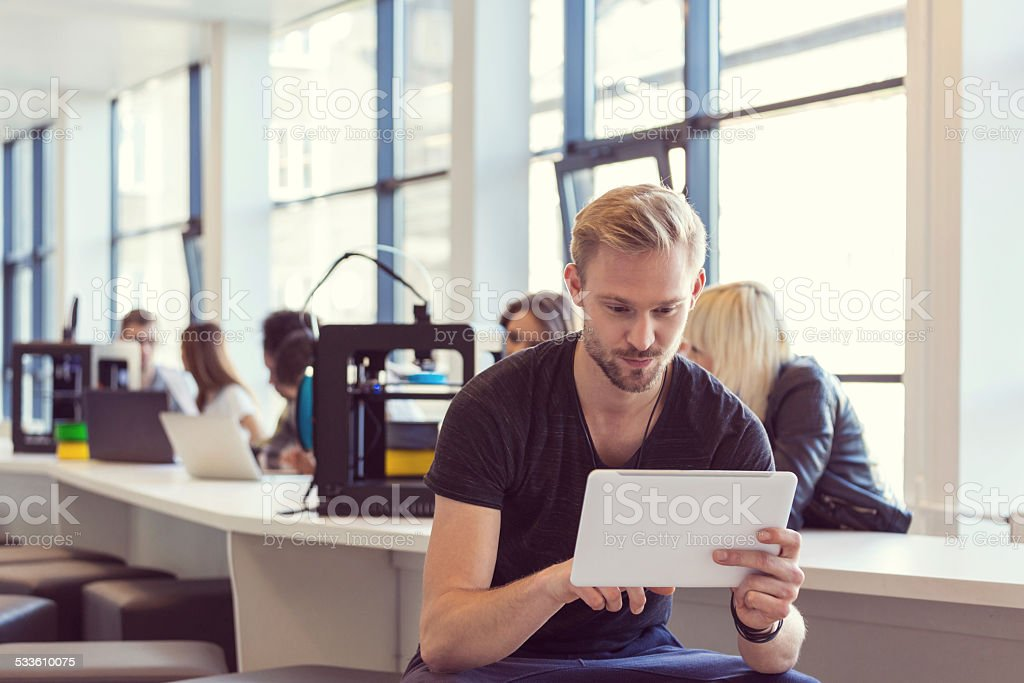 Young man using digital tablet in 3D printer office Focus on young man using a digital tablet with people working on 3D printers in the background.  2015 Stock Photo