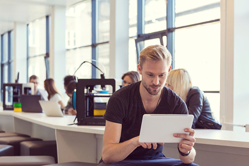 Young Man Using Digital Tablet In 3d Printer Office Stock Photo - Download Image Now
