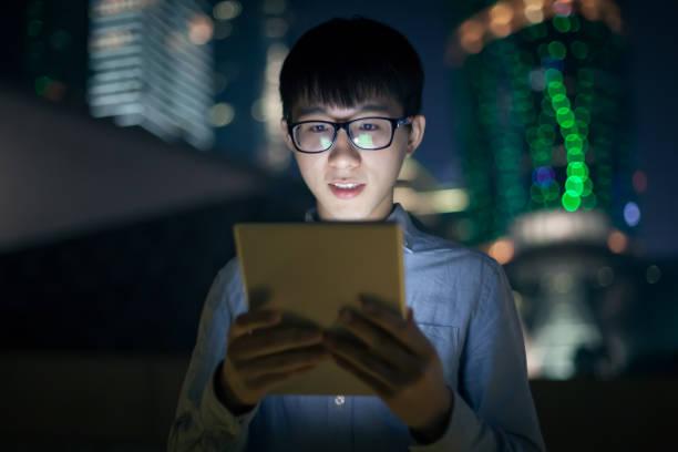 junger mann mit digitalen tablet im freien - pailletten shirt stock-fotos und bilder