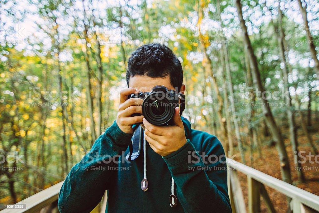 Young man using DSLR camera stock photo