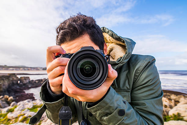 Young man using DSLR camera stock photo