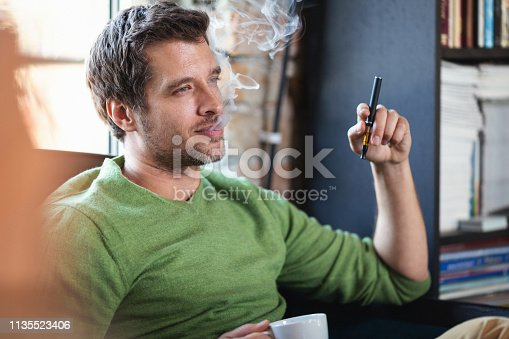 Young man using electronic cigarette. Shallow DOF. Developed from RAW; retouched with special care and attention; Small amount of grain added for best final impression. 16 bit Adobe RGB color profile.