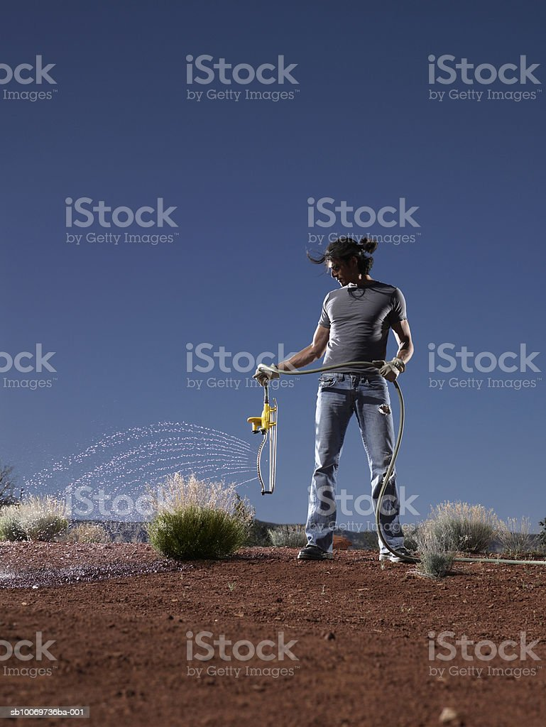 Young man using garden hose to water grass, front view 免版稅 stock photo