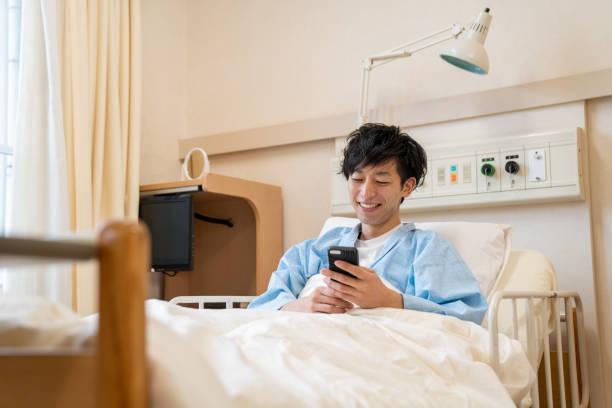 病院のベッドでスマートフォンを使用する若者 - 病棟 ストックフォトと画像