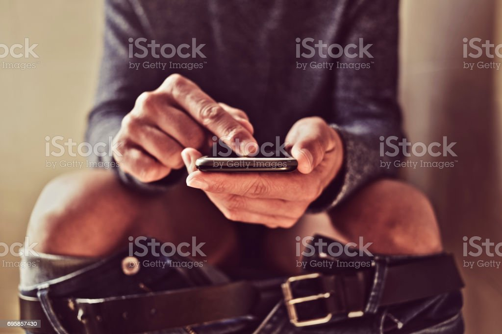 young man using his smartphone in the toilet stock photo