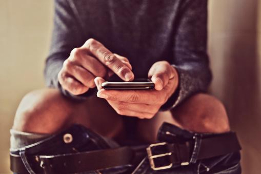 Hombre Joven Con Su Smartphone En El Baño Foto de stock y más banco de imágenes de Adicción