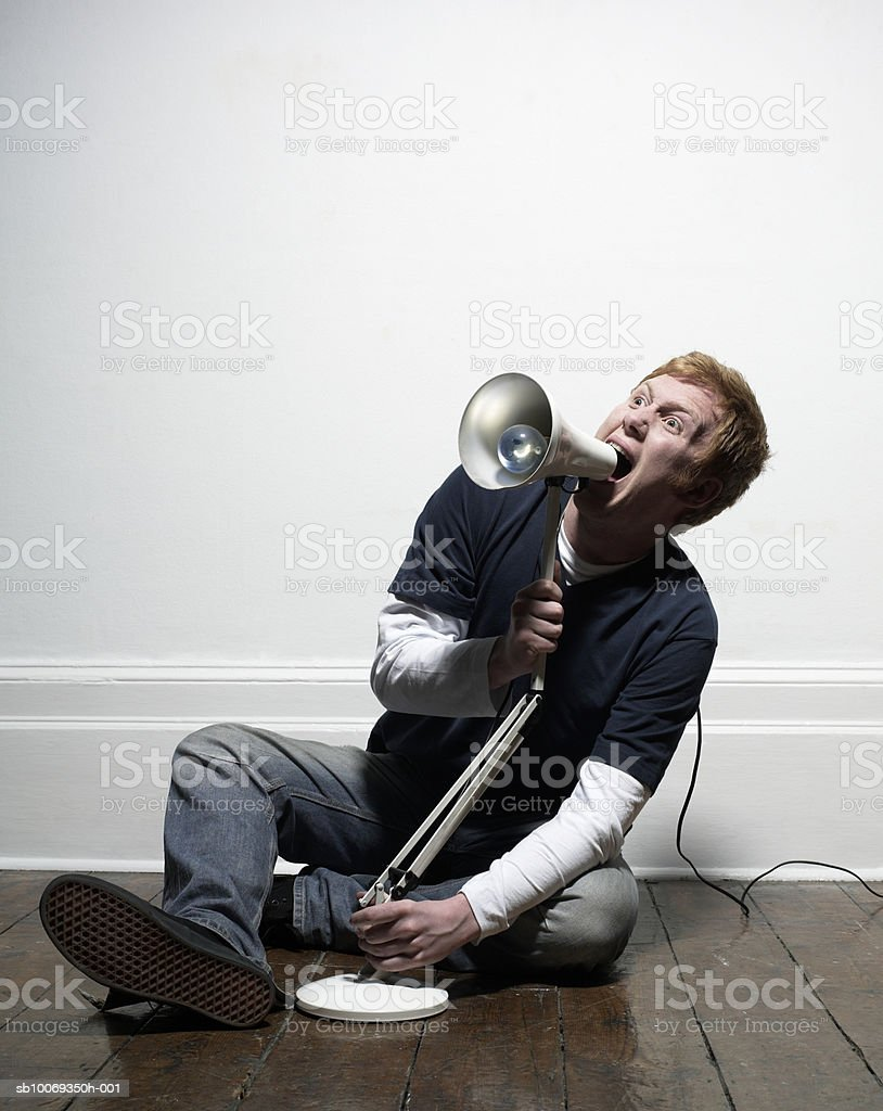 Young man using lamp as megaphone, indoors royalty-free stock photo
