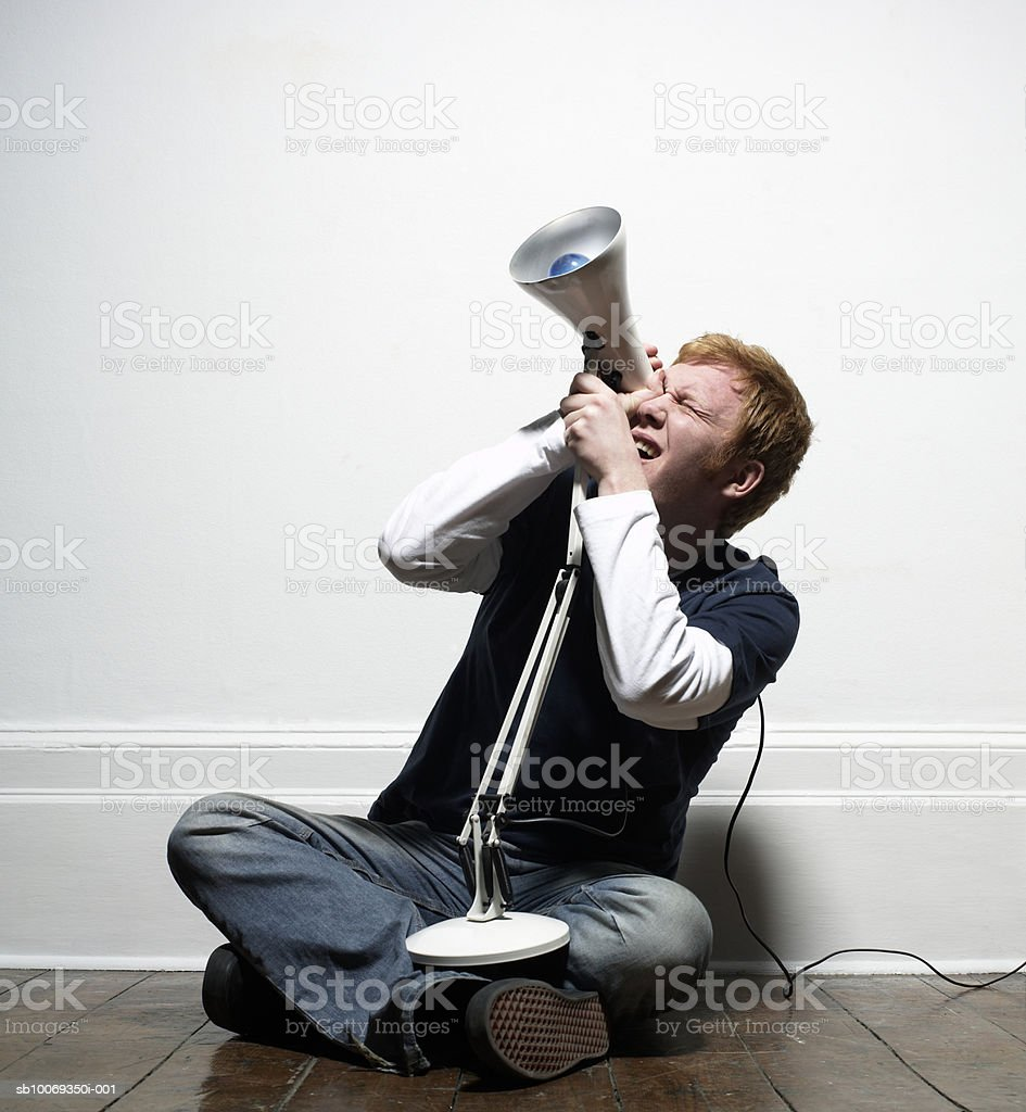 Young man using lamp as telescope, indoors royalty-free stock photo