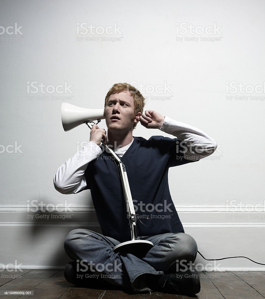Young man using lamp for hearing, indoors royalty free stockfoto