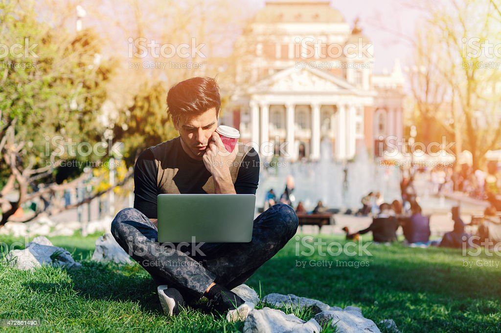 Young man using lap top outside stock photo