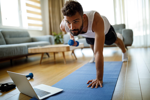 Young man using laptop and exercising at home